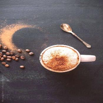 White coffee in a mug with thick foam, sprinkled with cinnamnon. Vintage silver spoon, coffee beans